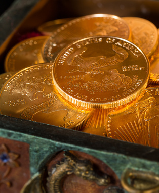 Stacks of gold eagle one troy ounce golden coins from US Treasury mint in old carved pirate treasure chest