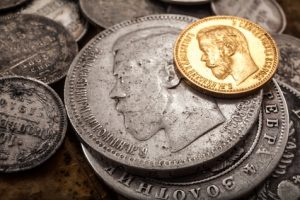 three silver and one gold ruble of the Russian Empire lie on dry leaves
