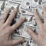 greedy hands cover one hundred dollar bills